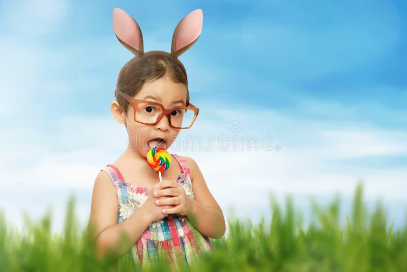 一个逗人喜爱的小女孩的画象在复活节兔子耳朵举行穿戴了 免版税图库摄影