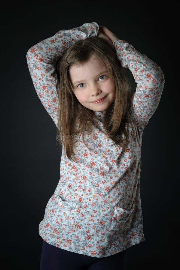 一个逗人喜爱的小女孩的画象用她的被举的手 免版税库存照片