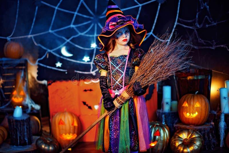 一个逗人喜爱的小孩女孩的画象一套巫婆服装的有不可思议的笤帚的 库存图片