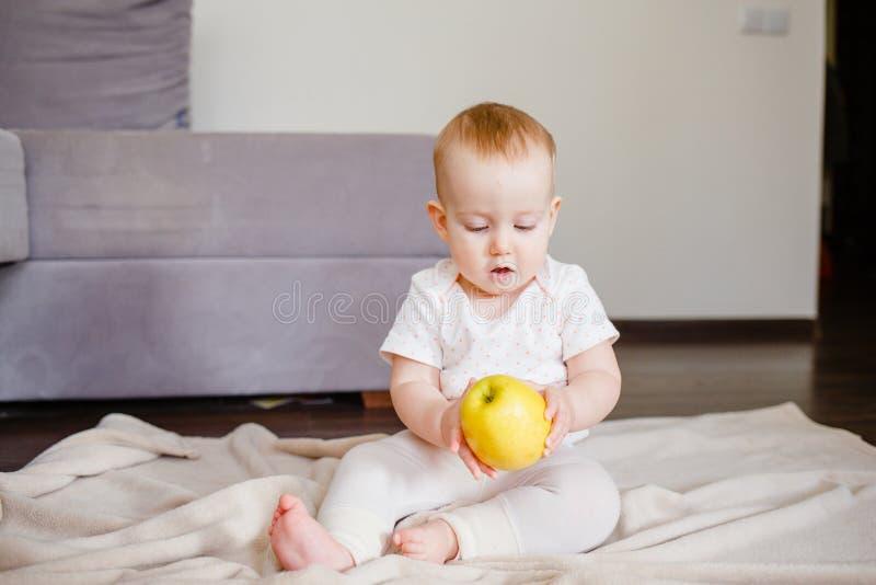 一个逗人喜爱的小孩的画象用一个黄色苹果,坐地板 女婴9个月大藏品果子 免版税库存图片