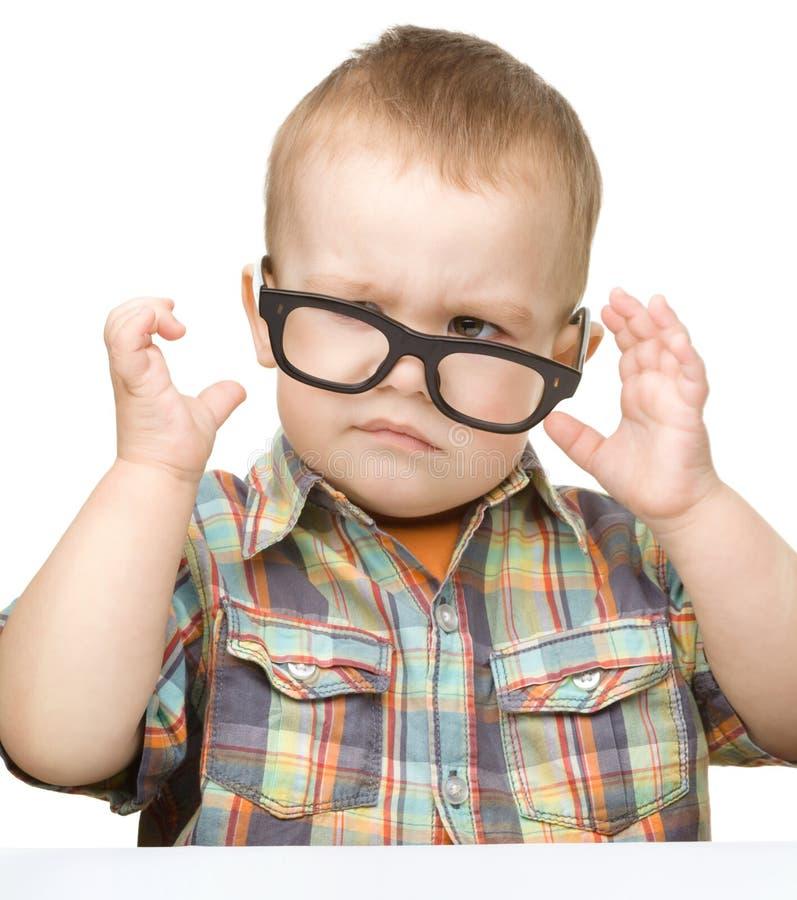 一个逗人喜爱的小男孩佩带的玻璃的纵向 免版税库存照片