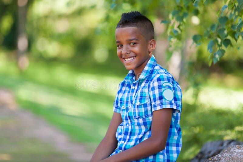 一个逗人喜爱的少年黑人男孩的室外画象-非洲人民 库存照片
