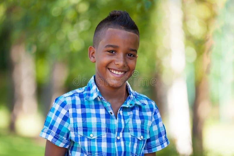 一个逗人喜爱的少年黑人男孩的室外画象-非洲人民 库存图片