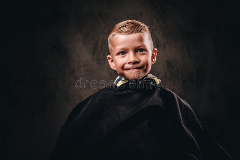 一个逗人喜爱的微笑的男孩的特写镜头画象坐与黑沙龙海角的一把椅子和等待美发师 免版税库存图片