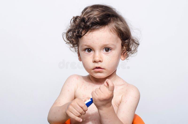 一个逗人喜爱的病的男婴的画象有拿着温度计的热病的 免版税库存照片