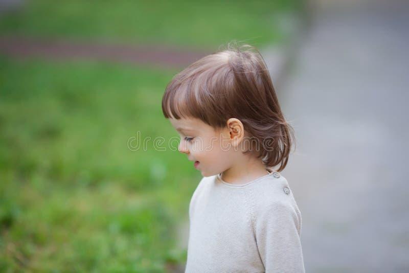 一个逗人喜爱的白肤金发的孩子的画象有长的头发的,穿戴在一件米黄毛线衣 三年的一个美丽的男孩 库存图片