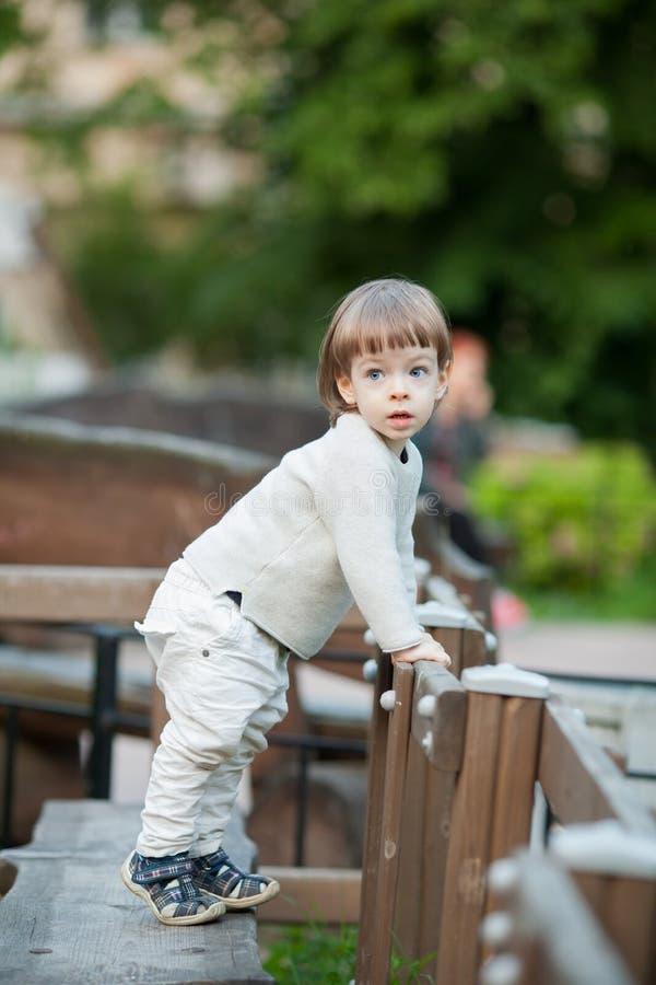 一个逗人喜爱的白肤金发的孩子的画象有长的头发的,穿戴在一件米黄毛线衣 三年的一个美丽的男孩 免版税库存照片