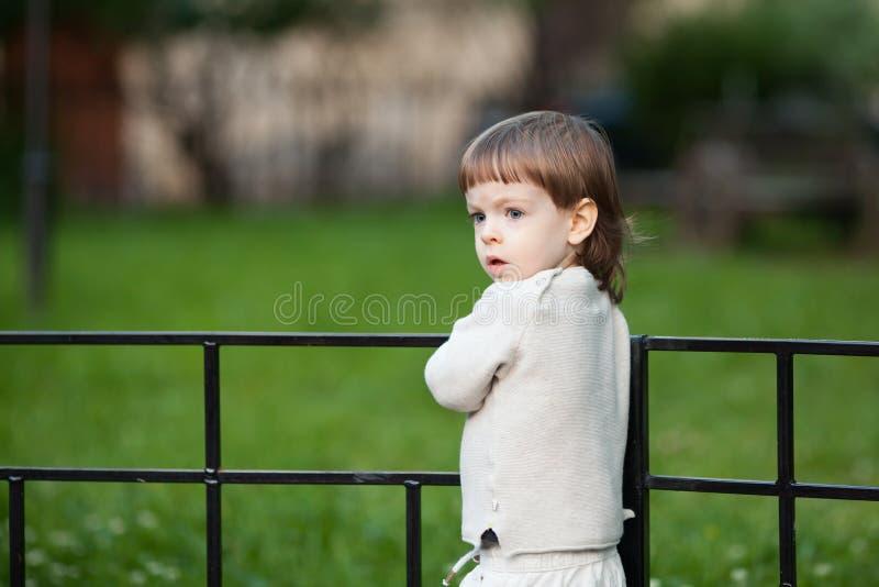 一个逗人喜爱的白肤金发的孩子的画象有长的头发的,穿戴在一件米黄毛线衣 三年的一个美丽的男孩 库存照片