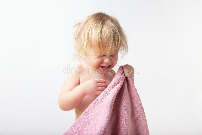 一个逗人喜爱的矮小的卷曲女孩的画象用特里毛巾,哭泣盖她的面孔害怕洗涤 育儿概念 免版税库存图片