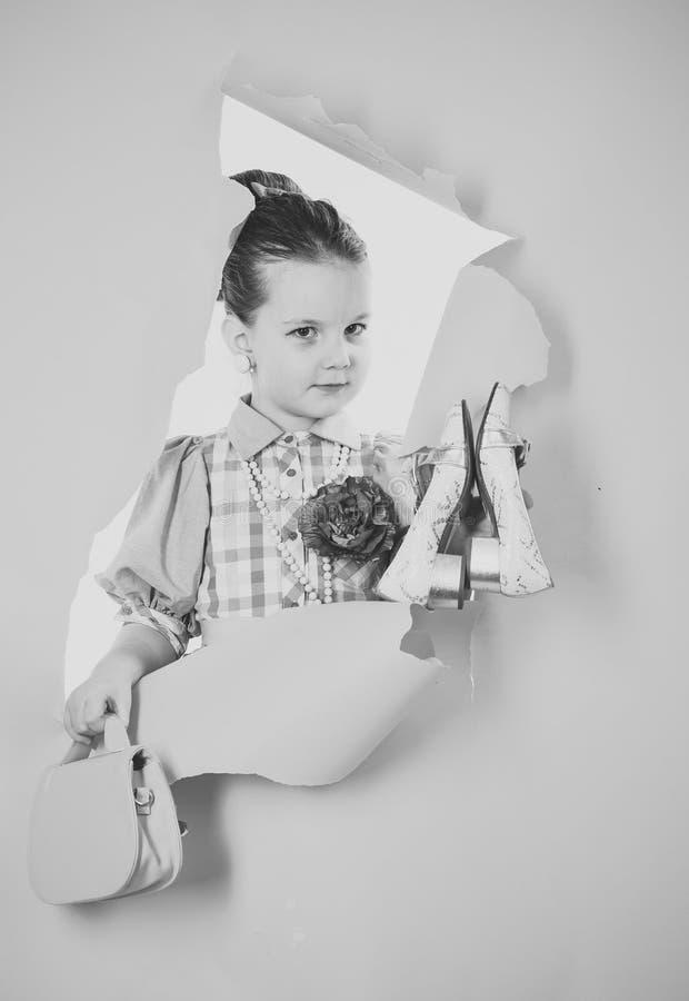 一个逗人喜爱的矮小的画报女孩的画象一件美丽的礼服、鞋子和袋子的 图库摄影