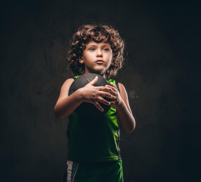 一个逗人喜爱的矮小的蓝球运动员的画象拿着球的运动服的在演播室 在黑暗织地不很细 免版税库存照片