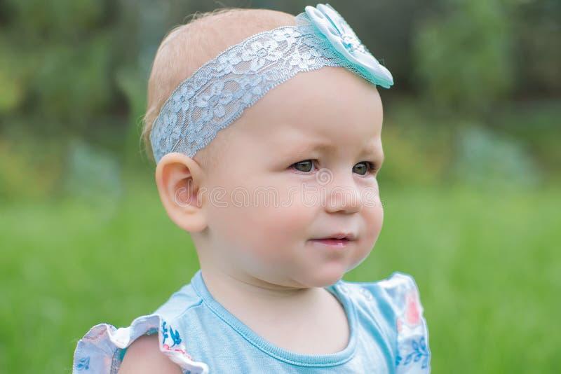 一个逗人喜爱的矮小的婴孩的画象有一把蓝色弓的 免版税库存照片