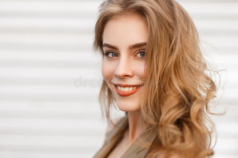 一个逗人喜爱的迷人的女孩的画象有美妙的微笑的与与卷发的自然构成有在白色背景的蓝眼睛的 图库摄影