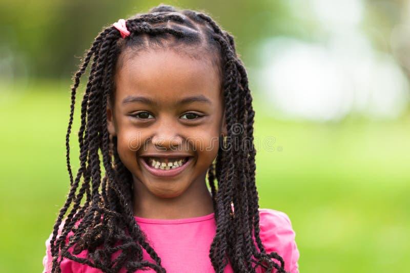 一个逗人喜爱的年轻黑人女孩的画象的室外关闭-非洲p 免版税库存图片