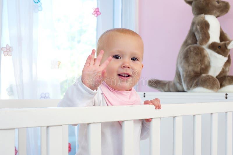 一个逗人喜爱的婴孩微笑的和挥动的你好的画象 库存照片