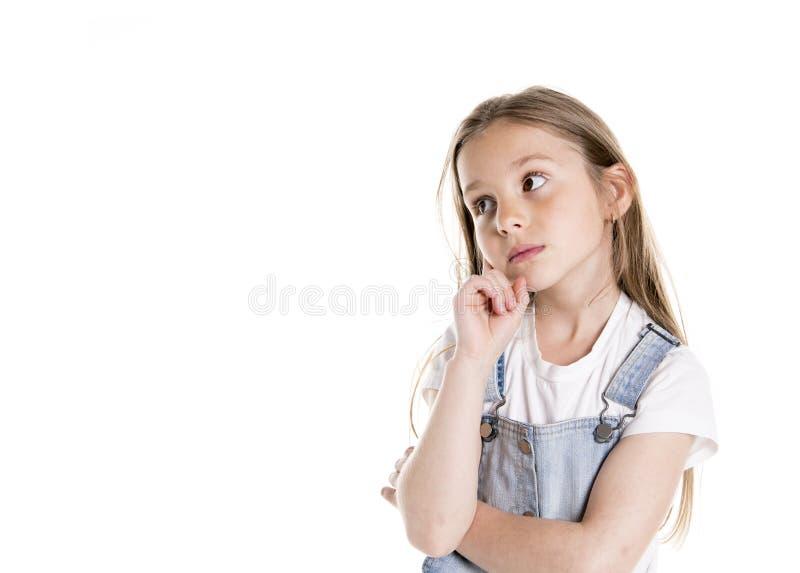 一个逗人喜爱的7岁女孩的画象被隔绝在沉思白色的背景 图库摄影