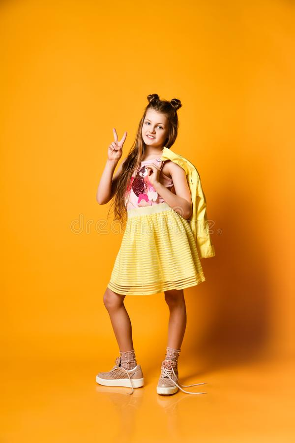 一个逗人喜爱,迷人的,可爱,快乐的十几岁的女孩的画象,显示在黄色背景的一个V标志和拿着夹克 库存照片