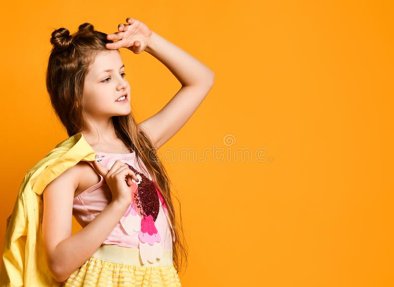 一个逗人喜爱,迷人的,可爱,快乐的十几岁的女孩的画象,看对在黄色背景的边和拿着夹克 库存照片