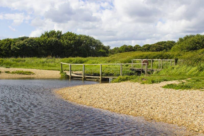 一个遥远的木人行桥在Titchfield共同性英国附近的勾子车道骑马专用路结束时 免版税库存图片