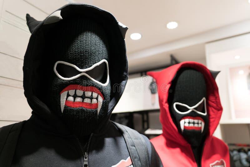 一个邪魔面具,一件夫妇滑雪衫在黑和红色服装在恶魔面具 库存图片