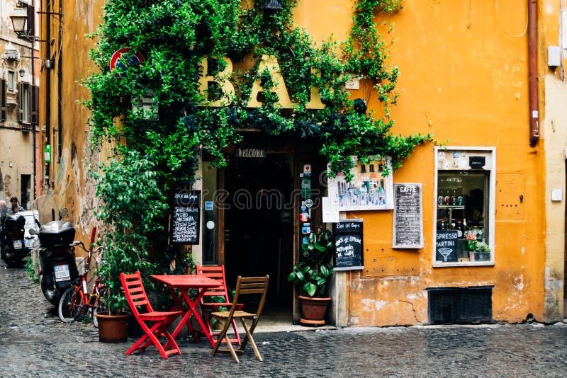 一个酒吧或咖啡馆的大阳台在罗马Trastevere,有红色椅子和桌的 温暖的口气和湿气在地板发光 库存照片