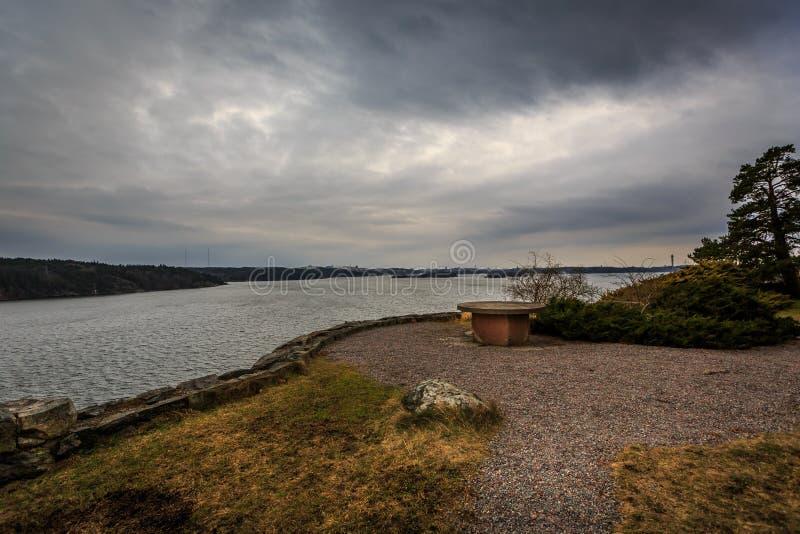 一个野餐休息区的美好的风景视图由水的与黑暗的剧烈的cloudscape 库存照片
