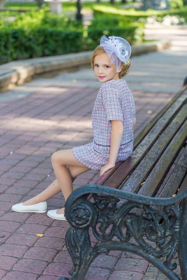 一个金发碧眼的女人的画象桃红色服装的在户外公园 免版税图库摄影