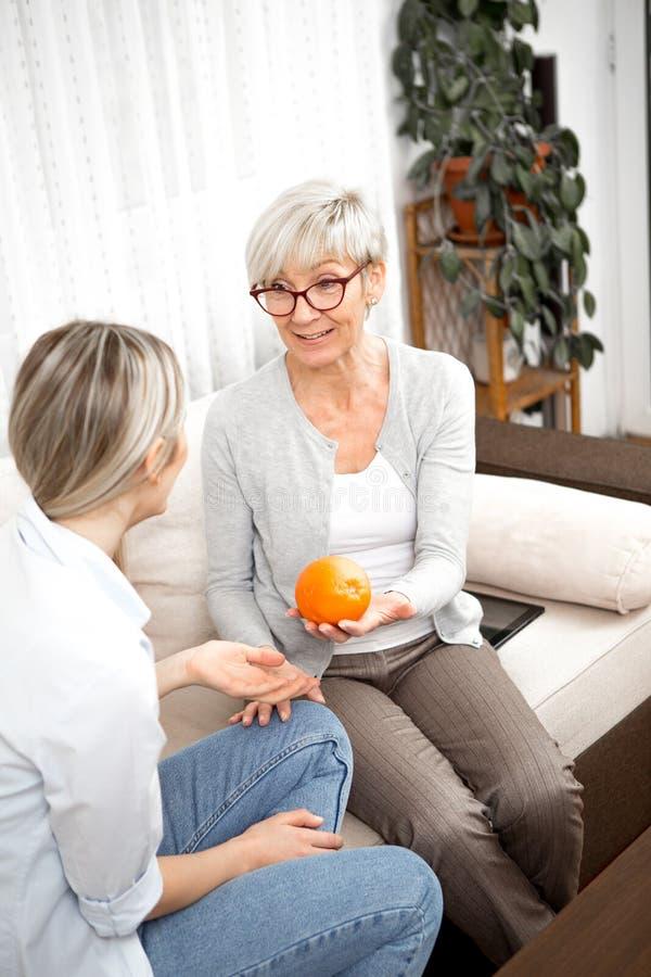 一个金发高龄女性给一个年轻女性橘子,因为健康饮食在生活中非常重要 它们位于 免版税库存照片