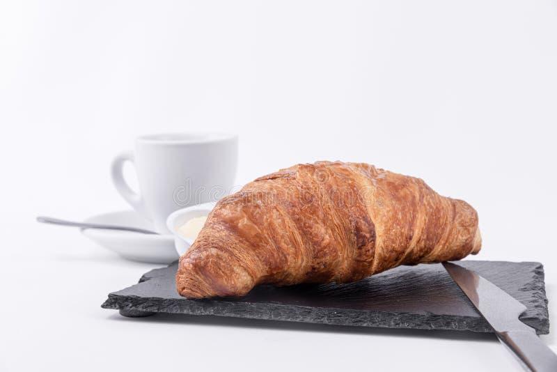 一个金黄新月形面包用黄油和咖啡在一个黑切板 库存图片