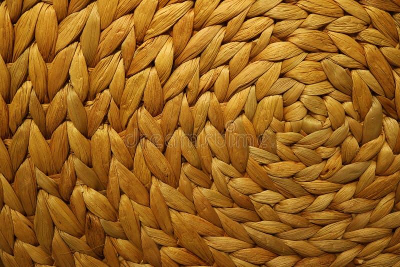 一个金黄棕色颜色被编织的凤眼兰位置字块的纹理和样式 免版税库存照片
