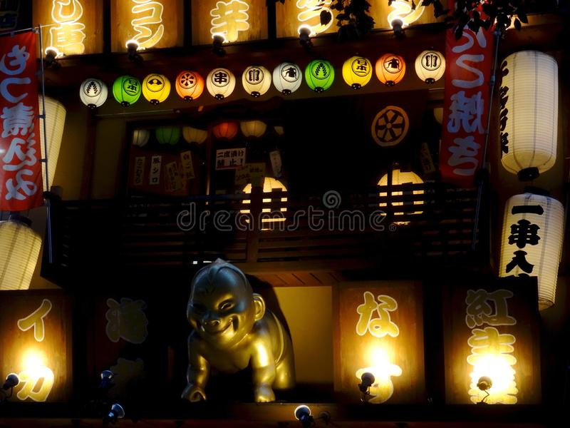 一个金黄Billiken一日本料理店的雕象和牌的接近的图片在大阪 库存照片
