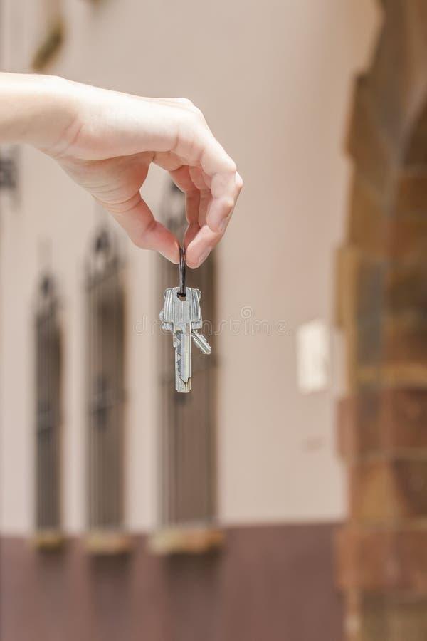 一个钥匙串公寓的在一个人的手上一个棕色房子的背景的 免版税库存照片