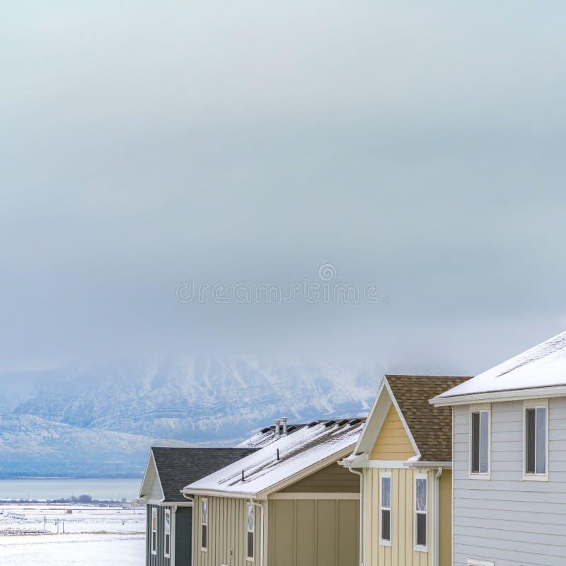 一个镇的清楚的方形的议院在冬天季节期间被观看的一座壮观的山附近 免版税库存图片