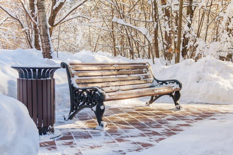 一个长木凳和一个垃圾箱在公园 图库摄影