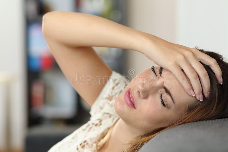 一个长沙发的主妇妇女有头疼的 免版税库存照片