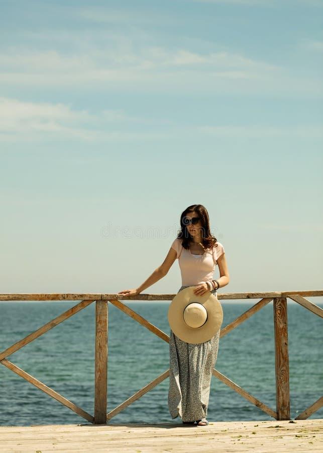 一个长的裙子和帽子的年轻美丽的妇女在木站立 免版税库存图片