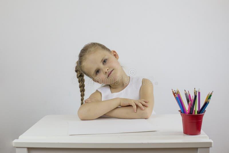 一个长辫子的美女坐在白桌前 图库摄影