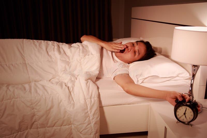 一个闹钟被唤醒的打呵欠的人在他的m的卧室 免版税库存图片