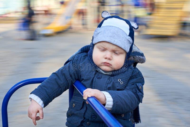一个阴沉的沉思小男孩在操场乘坐旋转木马 库存照片
