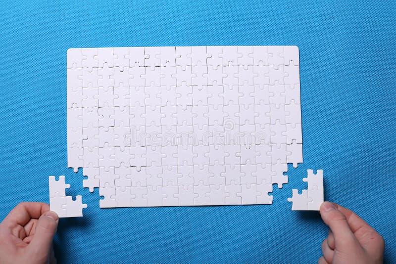 一个难题的白色细节在蓝色背景的 难题是pu 库存照片