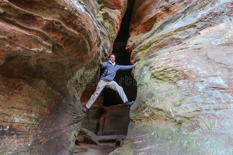 一个雄心勃勃的远足者在一个巨大的空隙决定上升 库存照片