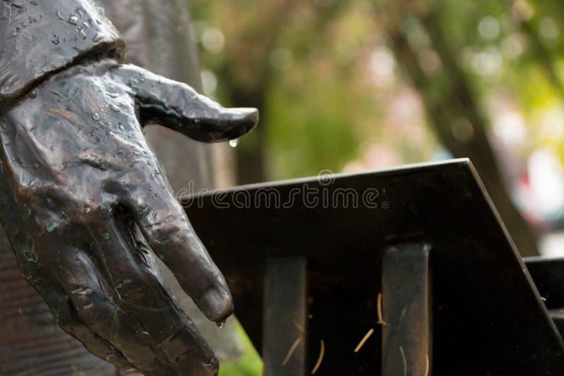 一个雕塑的金属手与雨珠的 免版税库存图片