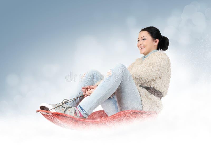 一个雪撬的女孩在雪 免版税库存图片