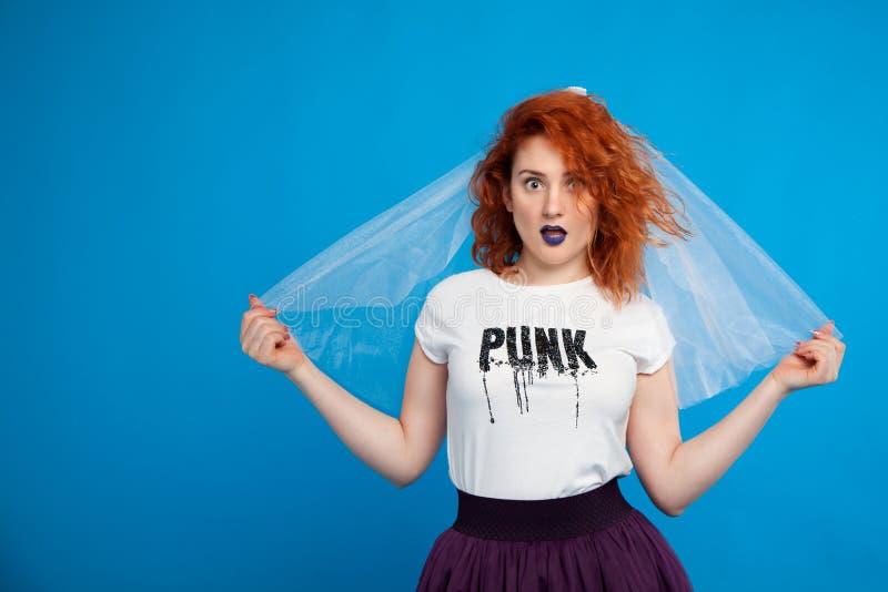 一个非凡新娘的红发女孩的被隔绝的画象,蓝色背景的,与蓝色嘴唇 安置fof文本 免版税库存照片