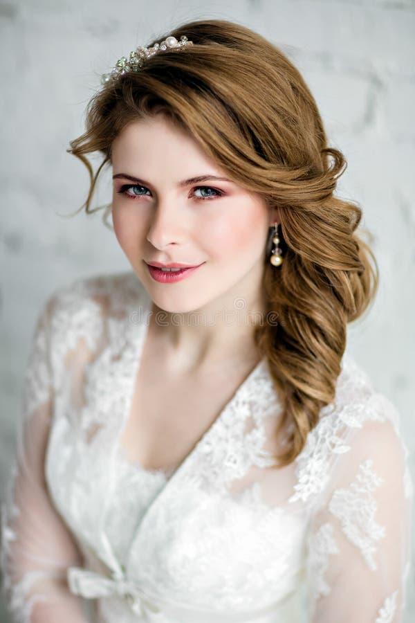 一个非常美丽的肉欲的女孩新娘的画象婚礼礼服的 图库摄影