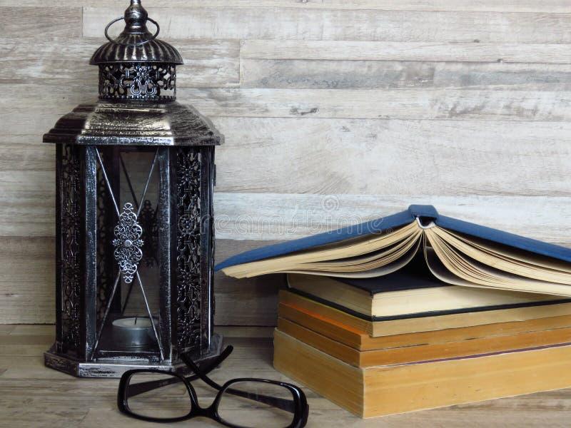 一个非常老银色灯笼,堆旧书,一副眼镜在被漂白的橡木背景的 免版税库存图片