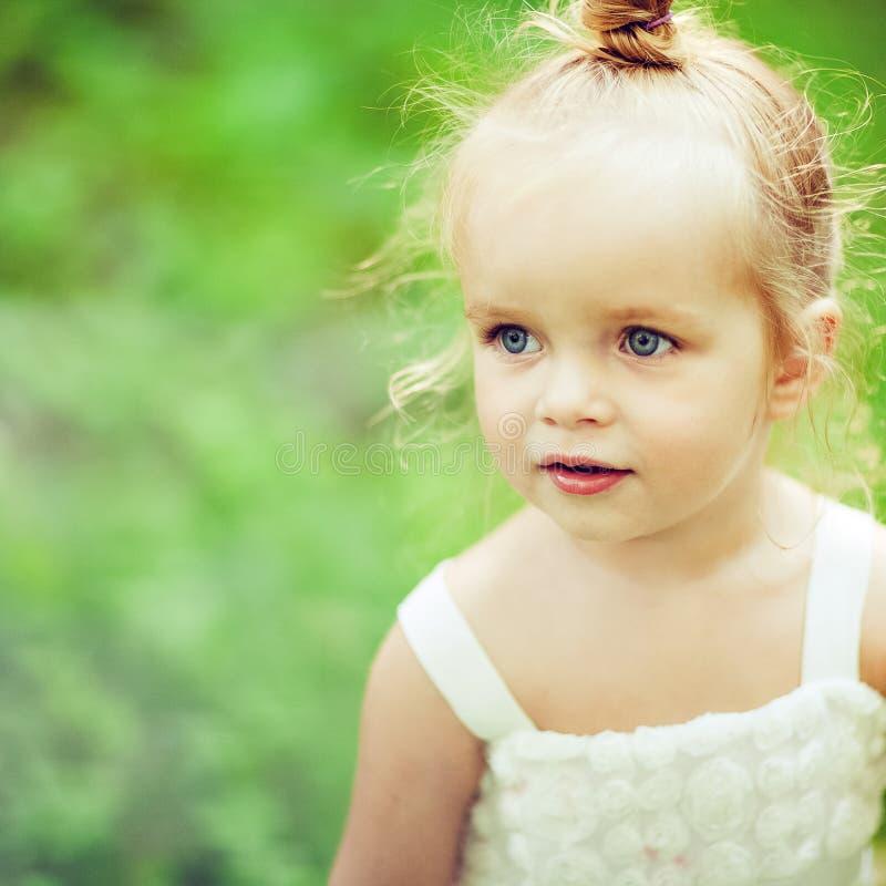 一个非常逗人喜爱的矮小的白肤金发的女孩的画象一件白色礼服的 免版税库存图片
