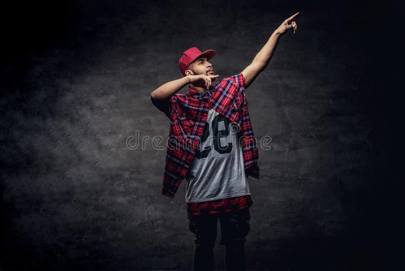 一个非裔美国人的舞蹈家人的画象在一个红色羊毛衬衣和盖帽穿戴了在演播室 隔绝在黑暗 免版税库存图片