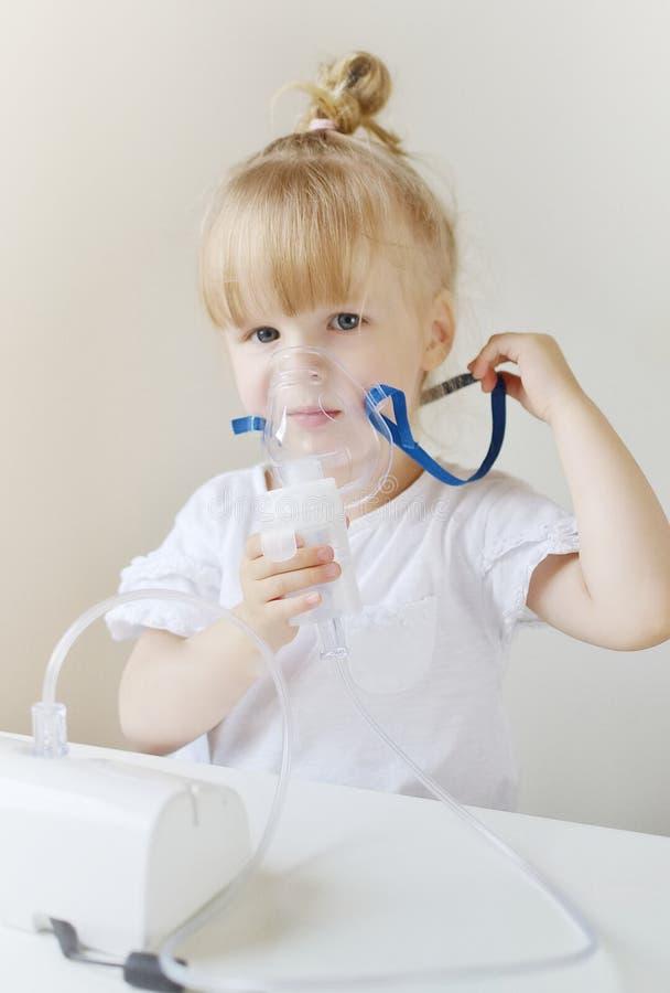 一个面具的小女孩吸入的,在家做与雾化器吸入器的吸入在桌 库存照片