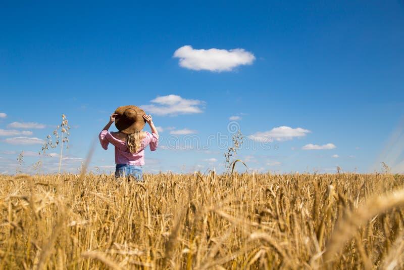 一个领域的女孩在麦子背景在蓝天Sunn下 图库摄影